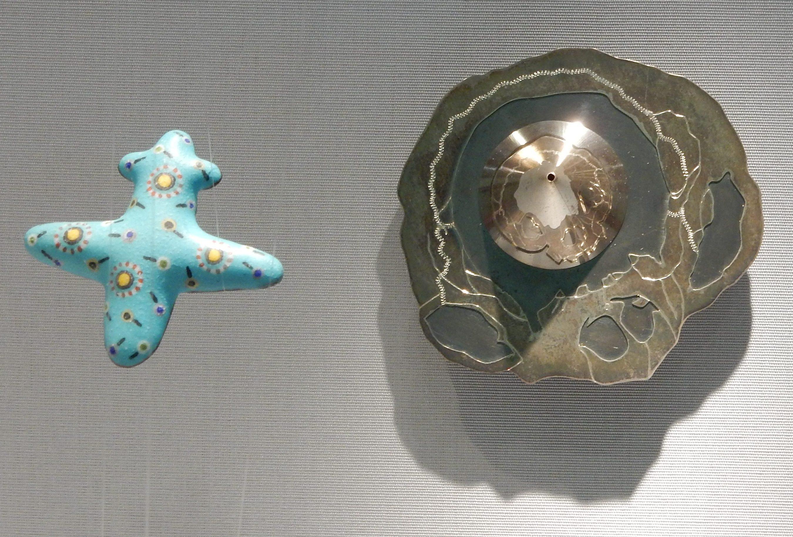 Wolfgang Lieglein, Flugzeug, broche, 1994, Johanna Dahm, Anamorphotische Brosche Schädel, broche, 1990. Schmuckmuseum Pforzheim. Foto Coert Peter Krabbe, metaal