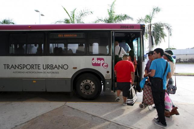 People stand in line to board a public bus in San Juan, December 1, 2015. REUTERS/Alvin Baez