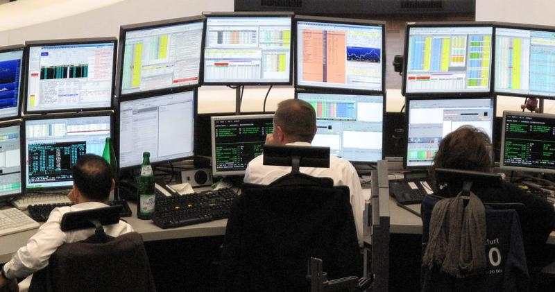 Traders are pictured at their desks at the trading room near by the DAX board at the Frankfurt stock exchange