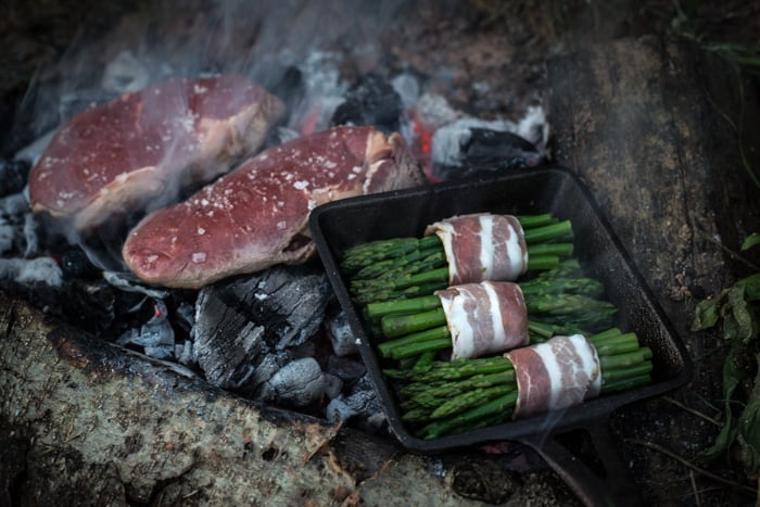 Asparagus and dirty steak cooking on an campfire