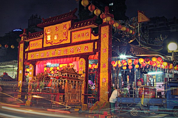 The temple is adorned in bright decorations and lanterns in honor of the celebration.