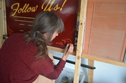 Rima paints scrolls in the corners of the signboards