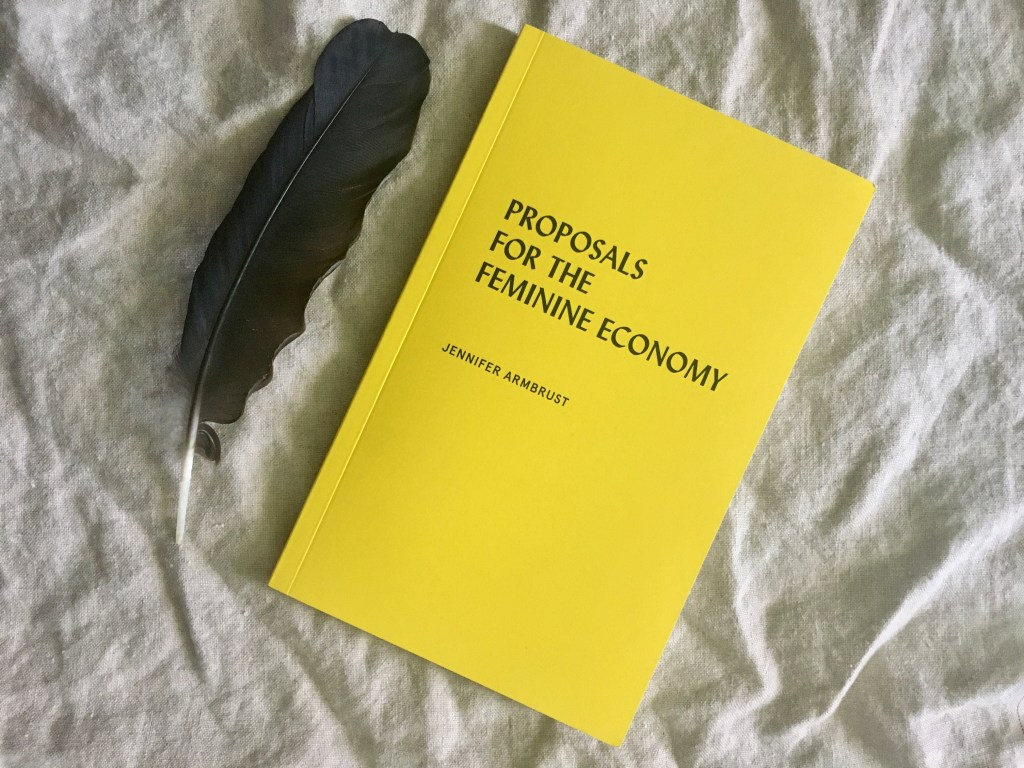 Bright yellow copy of paperback book Proposals for the Feminine Economy by Jennifer Armbrust sits on neutral linen background with single black crow feather