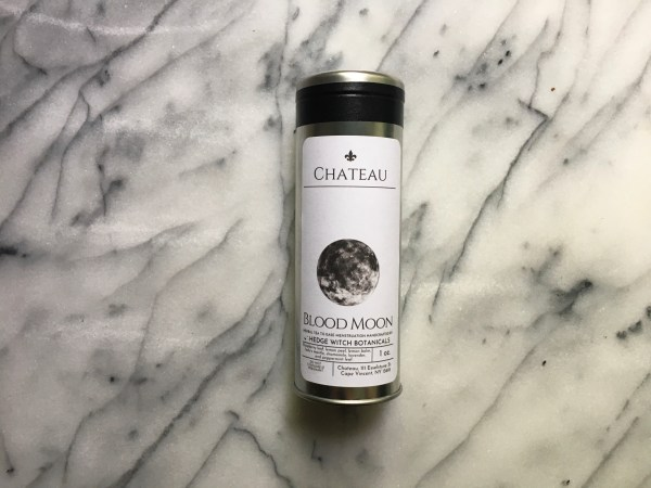 A tin of Blood Moon Tea on a marble background