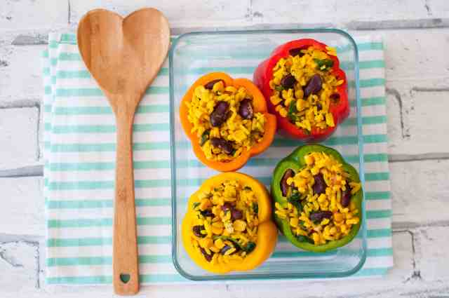 Clean eating stuffed peppers recipe made with turmeric rice, beans, corn and parsley. Easy, delicious and super quick #cleaneating #vegan #healthy
