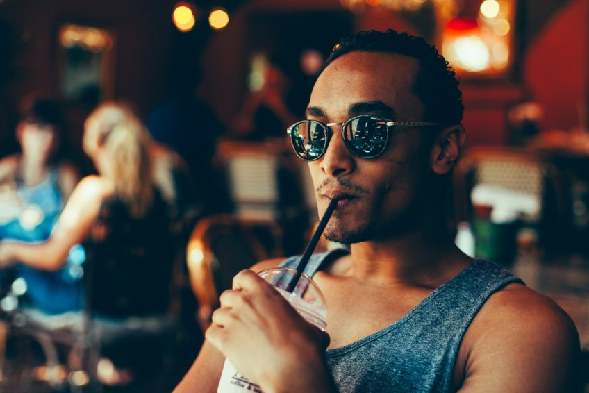 Guy with sunglasses drinking at bar
