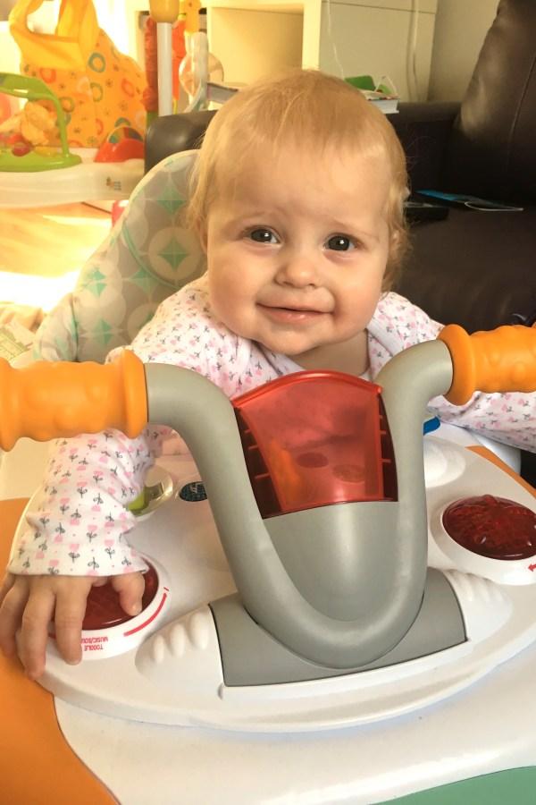 baby sitting in bike design walker, smiling over the  handlebars