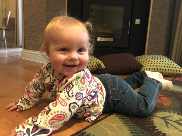 baby lying on tummy, holding chest and head up, smiling, in front of a fireplace