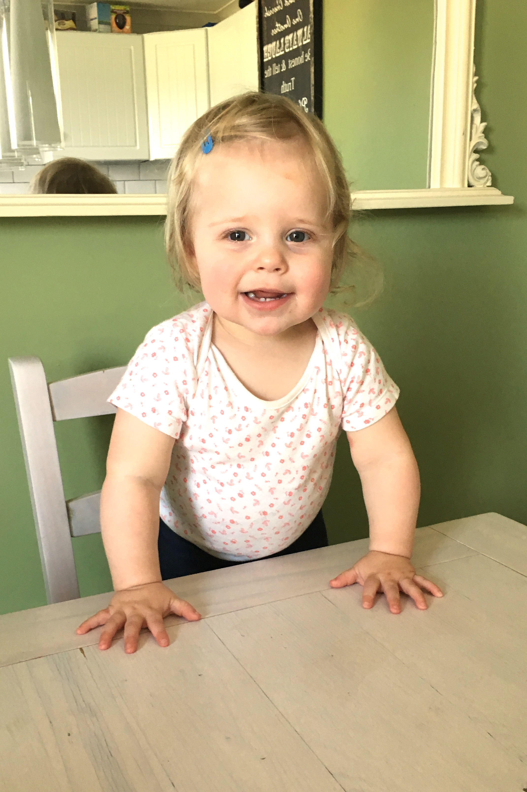 14 months old girl standing on dining room chair, leaning on table