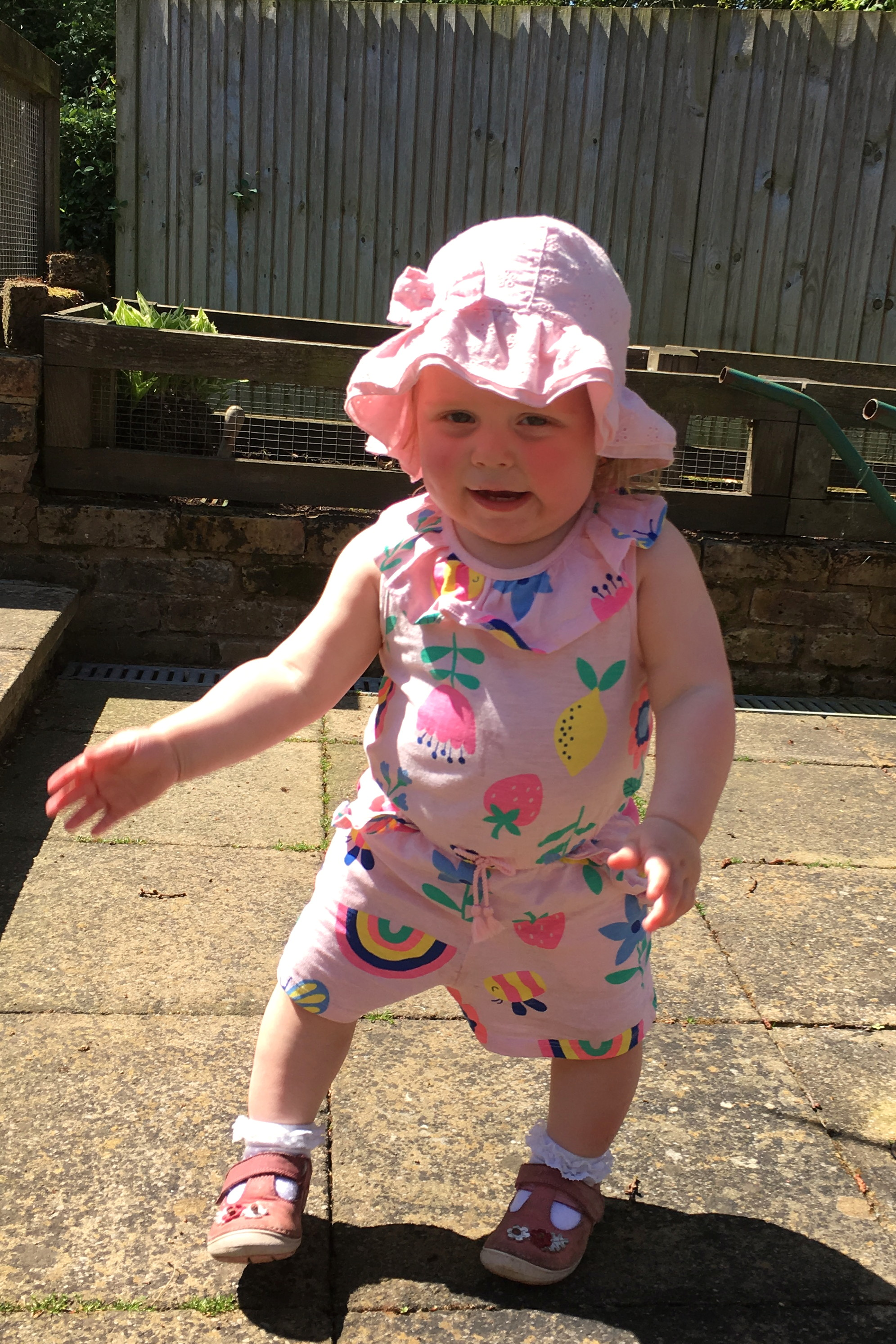 14 months old girl, dancing in the garden in sunshine