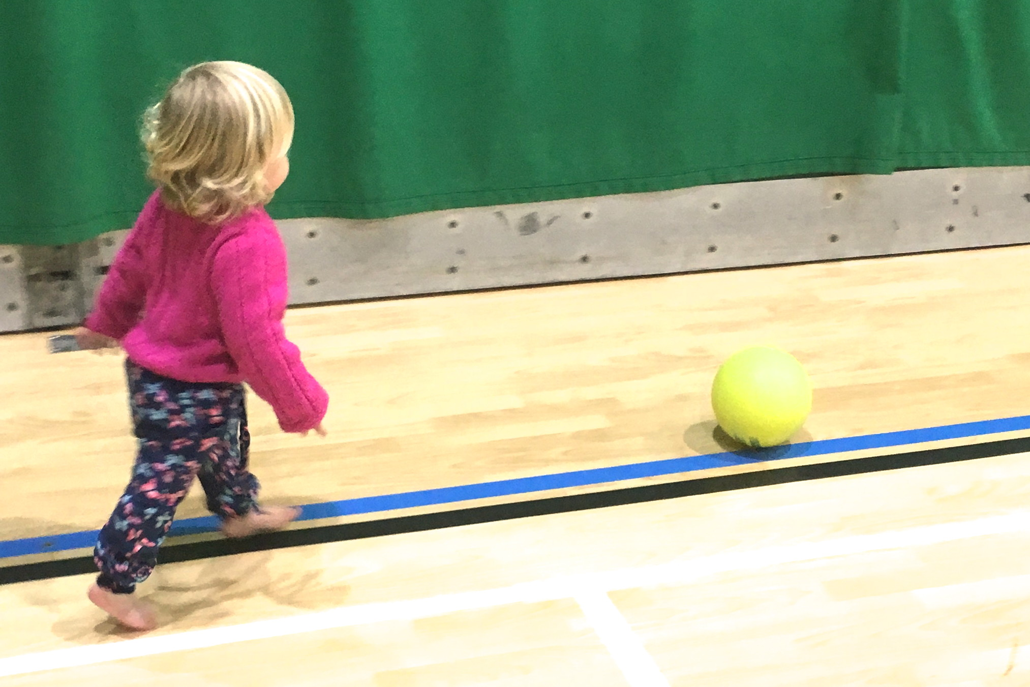 18 month old girl chasing ball in sports hall