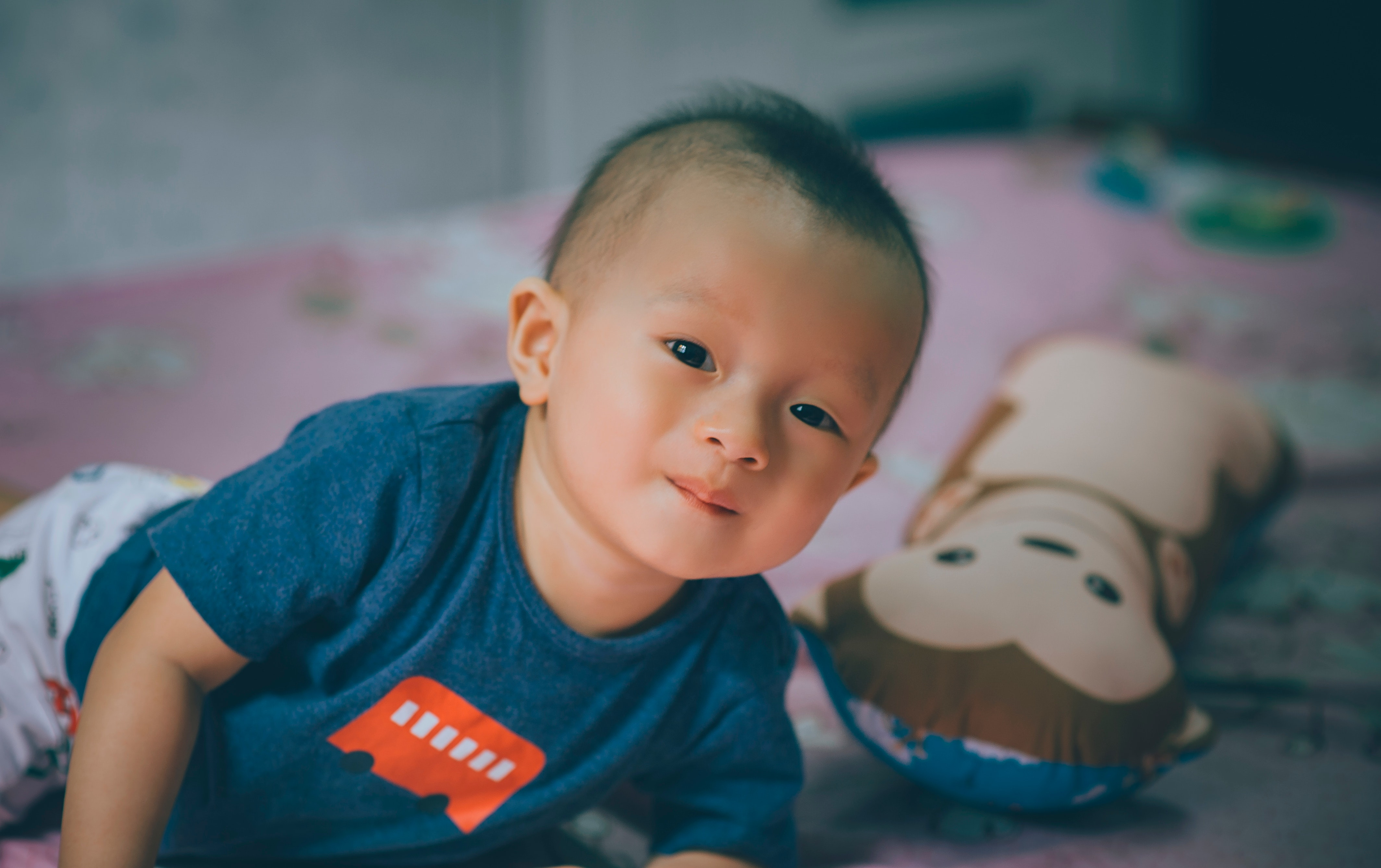 baby boy, lying on bed with teddy, smiling - when kids share a room