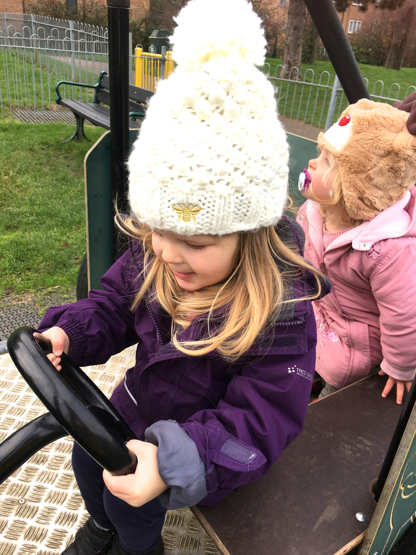 two sisters sitting on a climbing frame car, one pretending to drive