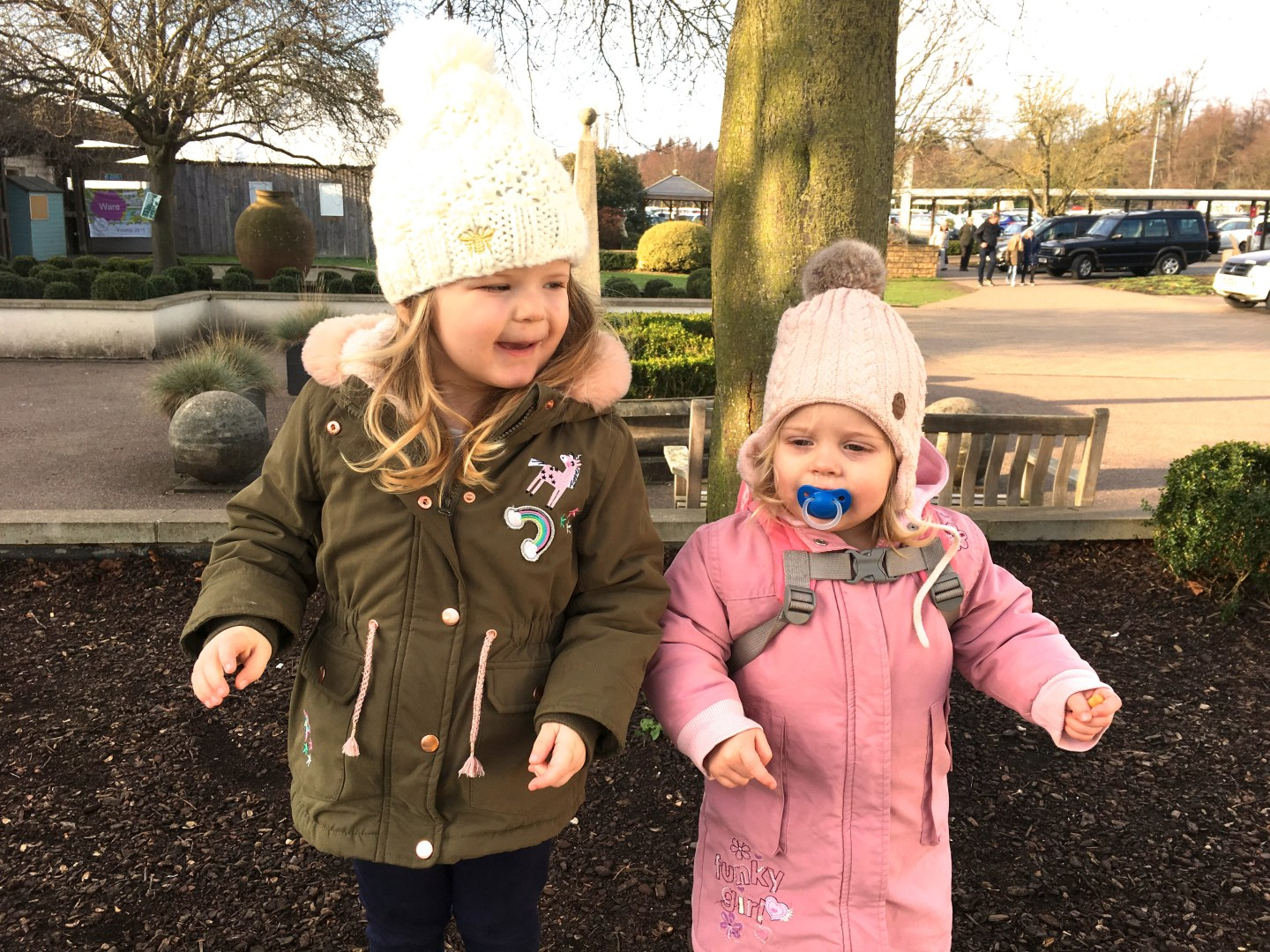 Two toddler sisters standing side by side on a wall in bobble hats and coats