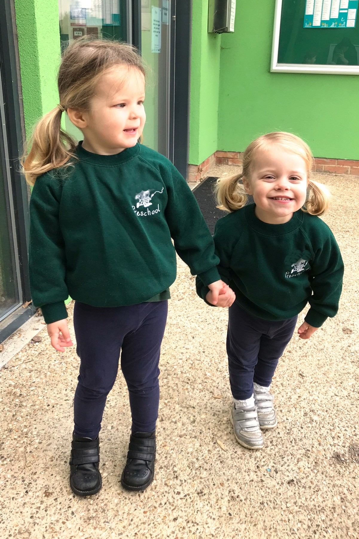 two sisters holding hands in preschool uniform, smiling