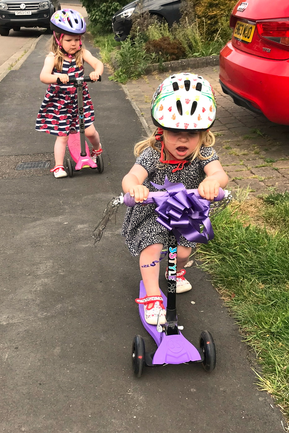 Two toddler sisters on scooters with helmets on, scooting down a pavement
