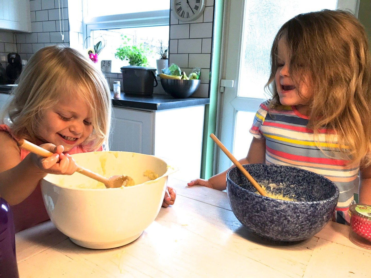 two little sisters, sitting at a table with a mixing bowl and wooden spoon each
