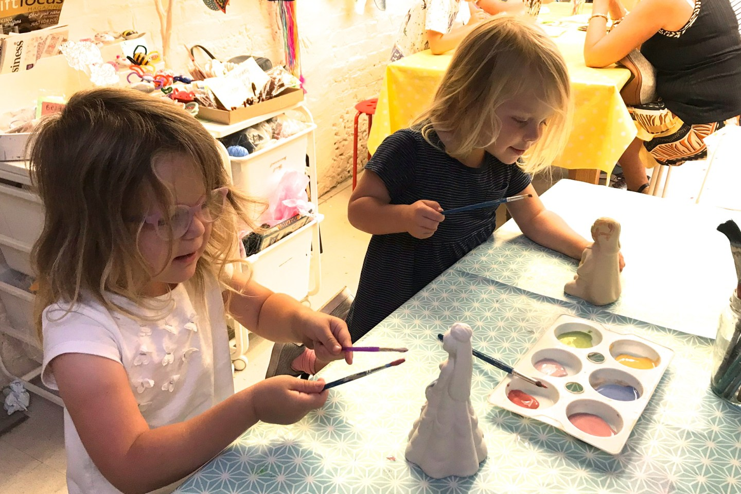 Two sisters painting pottery