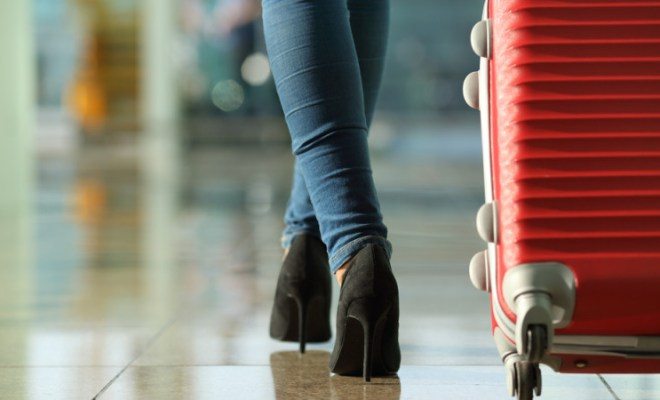 woman in heels with carryon luggage