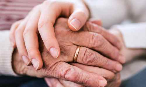 Elderly hands being clasped by younger hands in a loving way after discussing Guardianship.