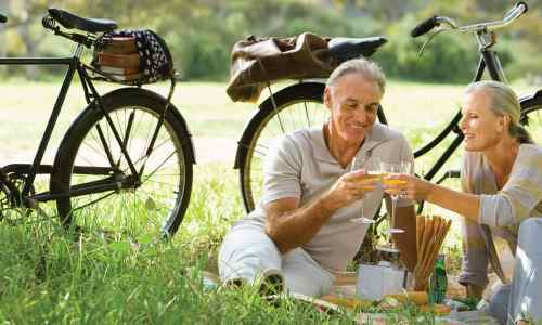 A elderly couple having a break from their bike ride enjoying a picnic in the country side