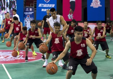 NBA Star Jeremy Lin helps a young player during a basketball camp in Beijing, China, Aug. 25, 2013. | AP Photo
