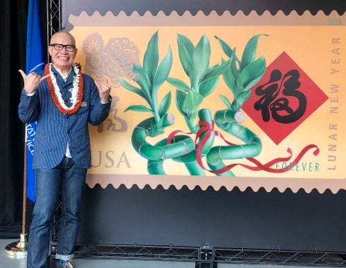 Kam Mak stands next to an image of the Year of the Dog stamp he created, which was dedicated in Honolulu. Mak is giving the friendly Hawaiian shaka sign, which means hang loose. Photo credit: Heidi Chang