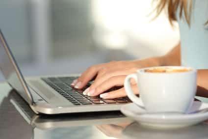 Frau textet in Heimarbeit auf Laptop