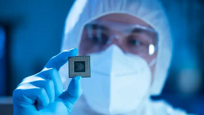 Manufacturing employee holds microchip
