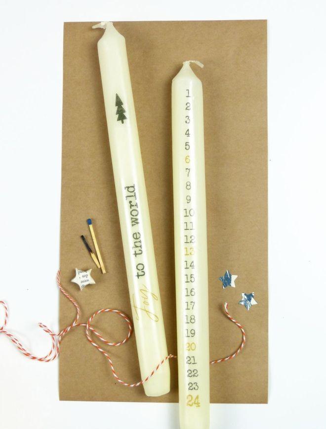 Zwei Kerzen mit Adventskalender Ziffern und einem Spruch