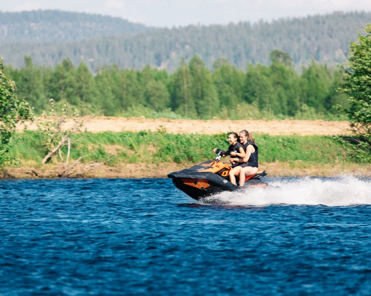 Women enjoying a water scooter ride in Torne River in Norrbotten, Sweden during the summer.