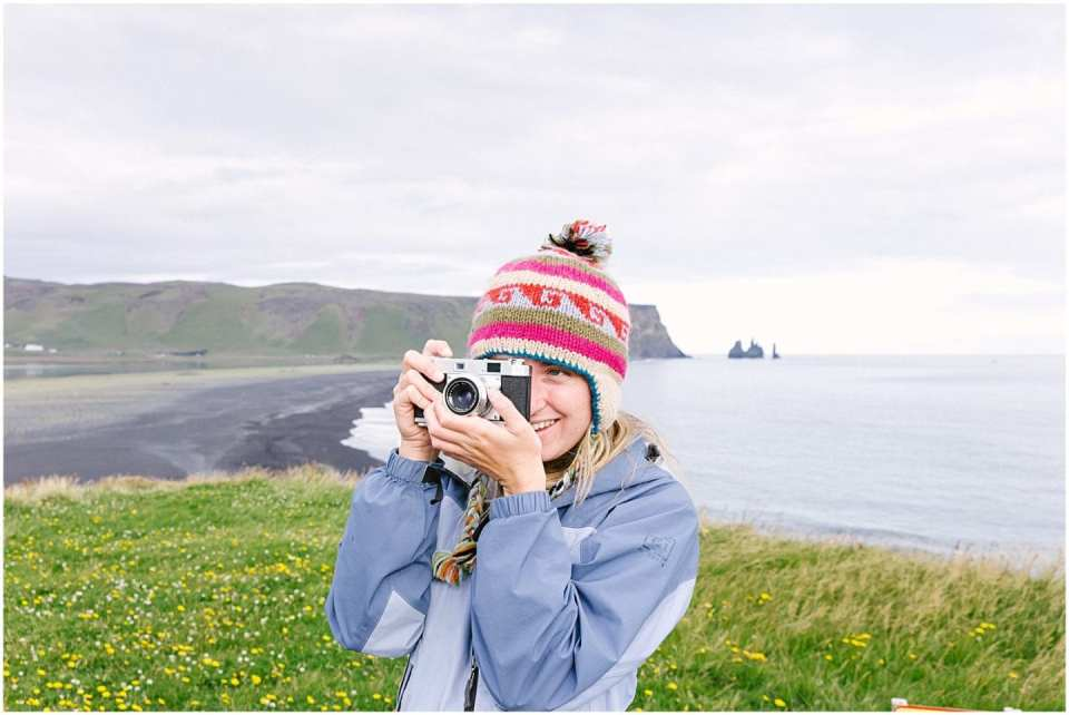 girl taking photo from a film camera while taking a technology free vacation in iceland