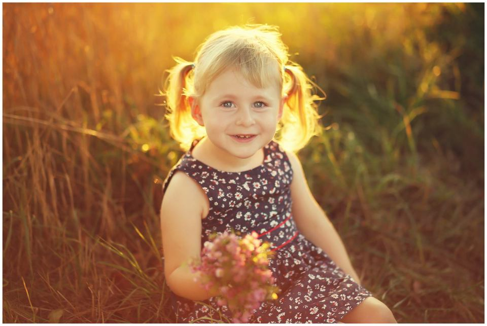 girl surrounded by golden natural light in field photographed by Helena Woods Photography