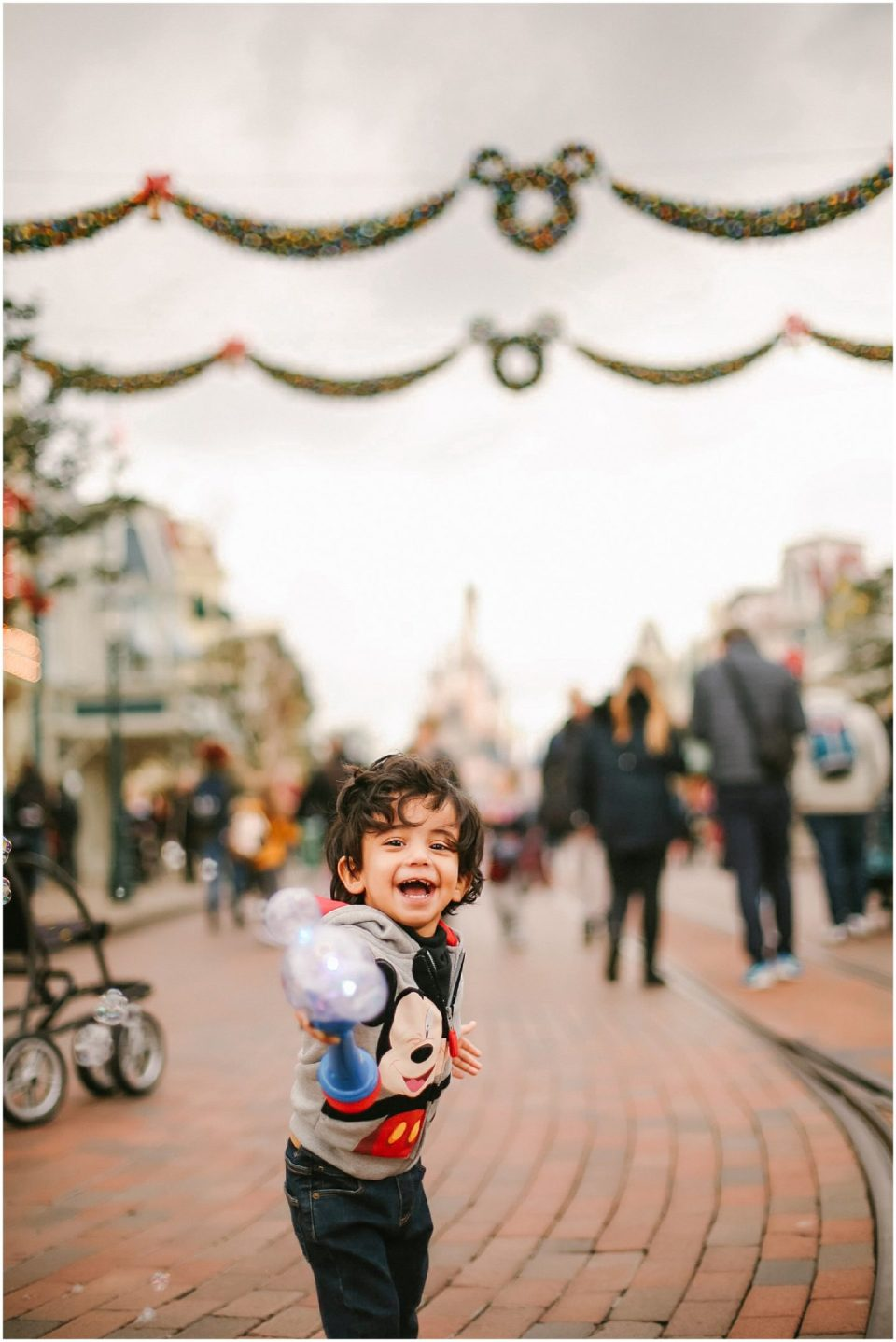 child with bubbles on Main Street Disneyland Paris with Disney vacation family photographer | Helena Woods Photography