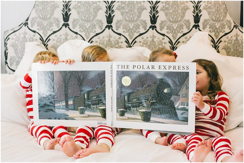 sibling children reading The Polar Express in matching christmas pajama outfits