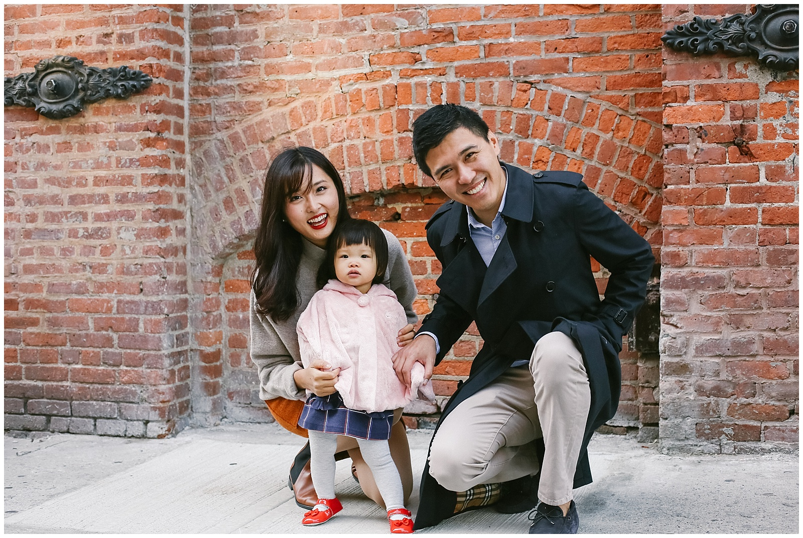NYC family photographer photographs smiling asian family in DUMBO Brooklyn