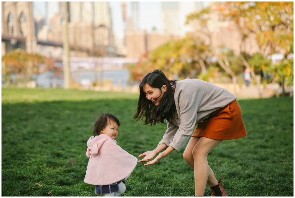baby girl and mother playing with nyc photographer in DUMBO brooklyn bridge