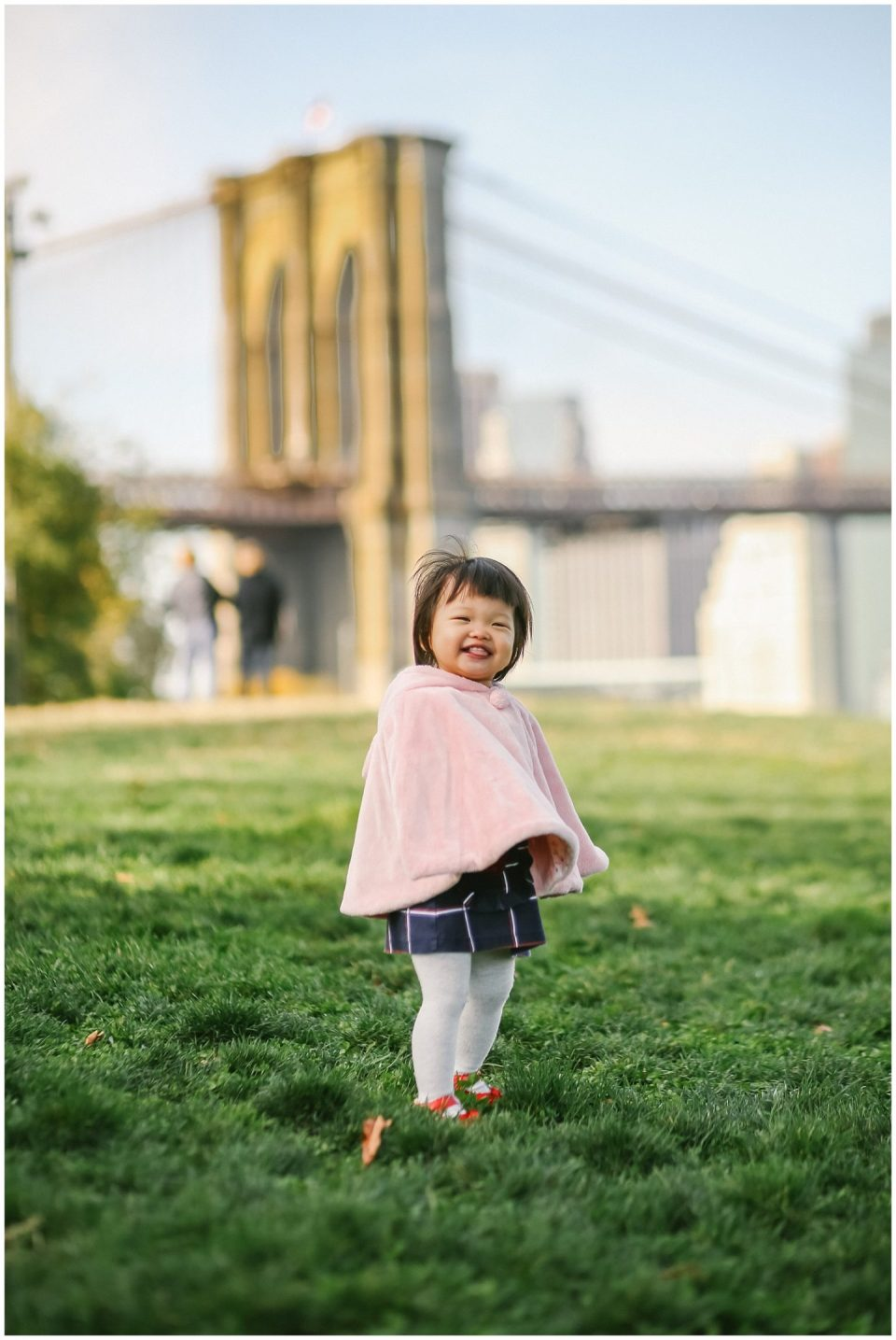 baby girl smiling for nyc family photographer in DUMBO Brooklyn bridge