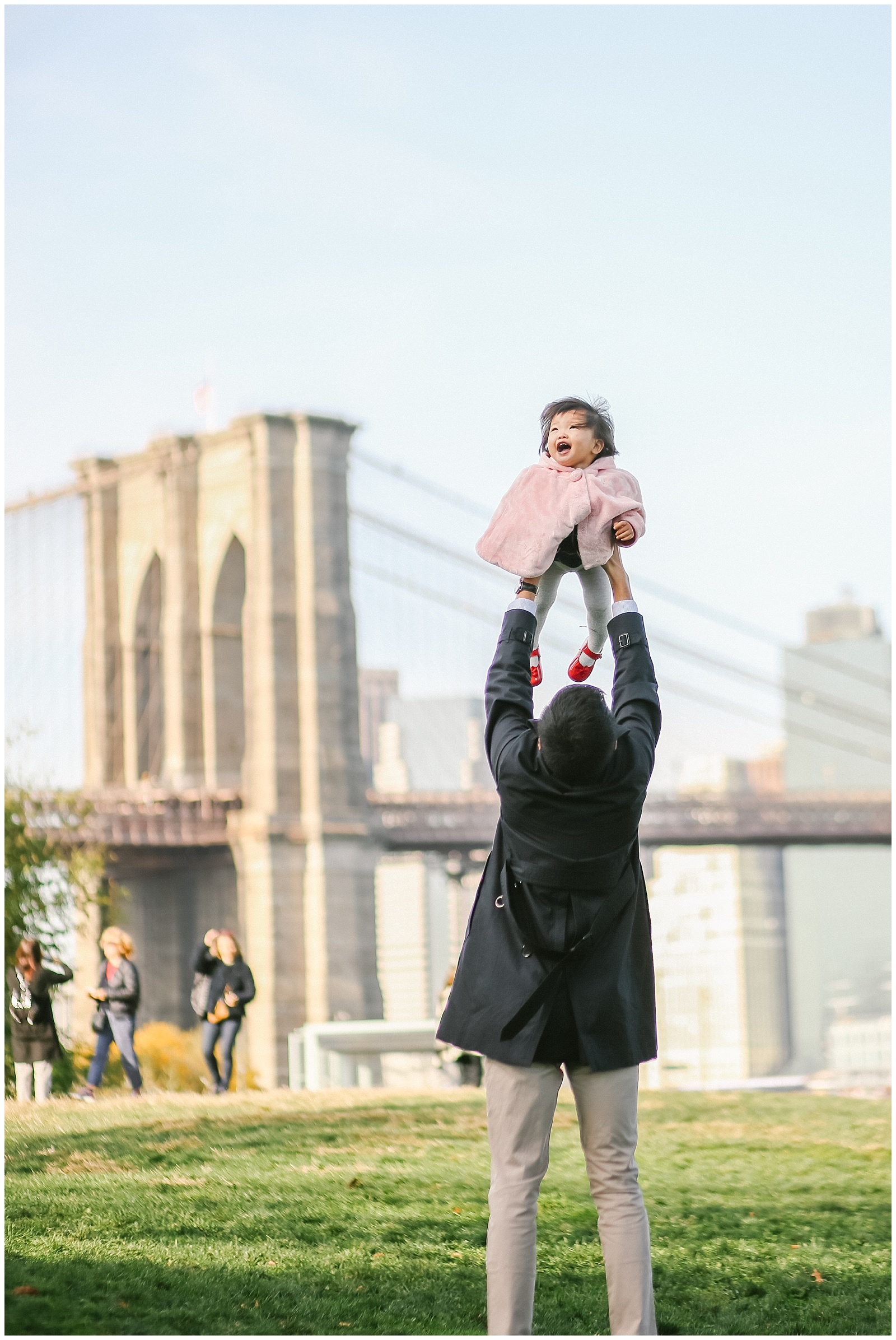 dad plays with baby in Brooklyn Bridge park in dumbo with NYC Family photographer Helena