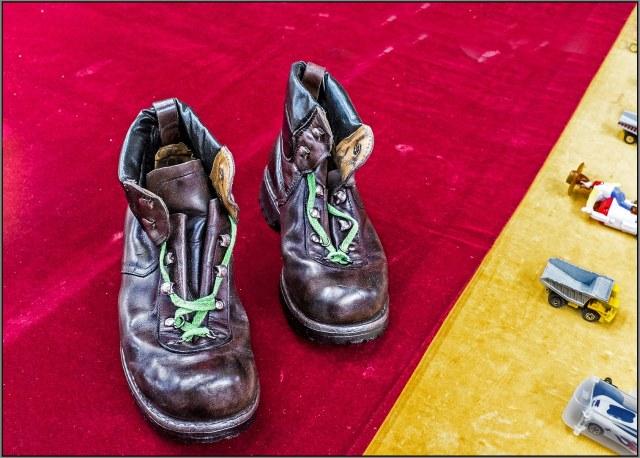 old boots on red velvet beside Matchbox cars