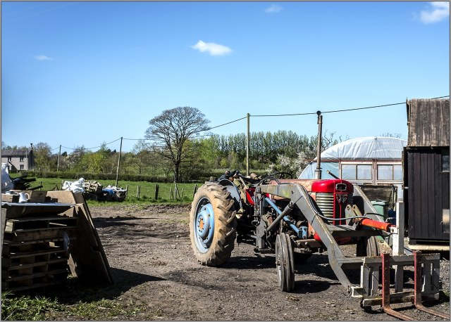 Red and bluet tractor in farmyard beside Lancaster Canal