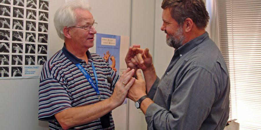 Hans Driksen en Ton Geers demonstreren vierhandengebarentaal