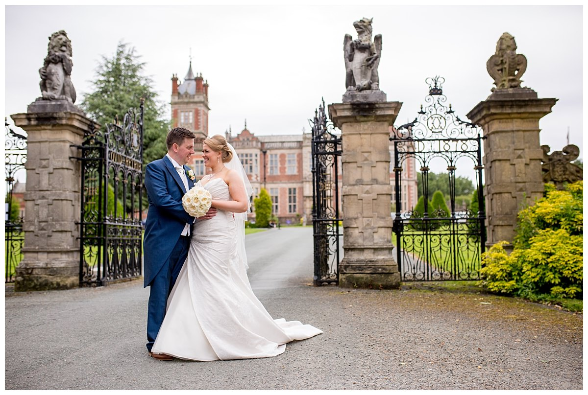 Bride and groom outside the gates of Crewe Hall