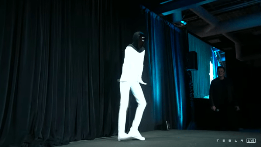 Elon Musk looks on at a dancing robot.