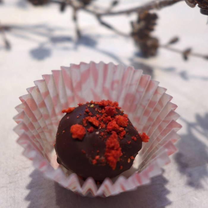 Trøflene er blandet med krokan (ristede nøtter og karamell som er hakket grovt). Mørkt sjokoladetrekk og pulverisert jordbær på toppen.