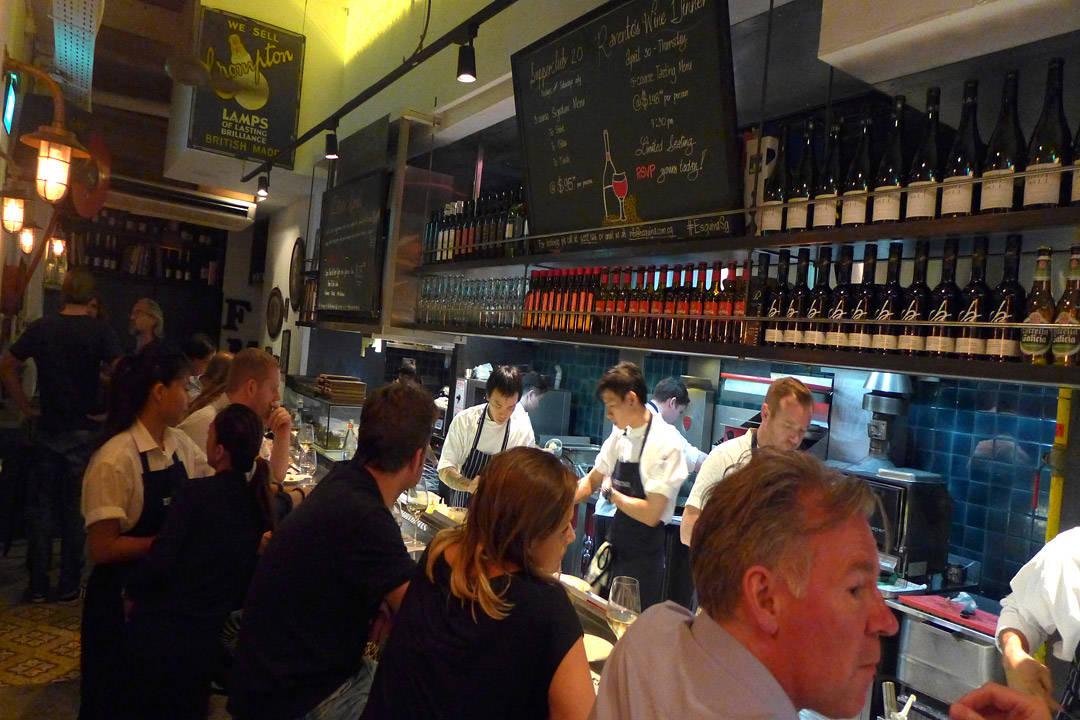 Esquina i Singapore. Man spiser på bardisken og ser kokkene jobbe.