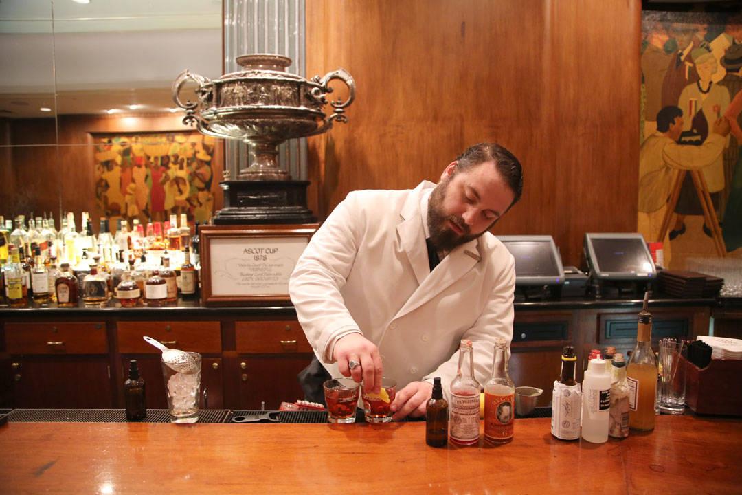 Bartenderen gnir sitronskall på kanten av Coctailglasset.