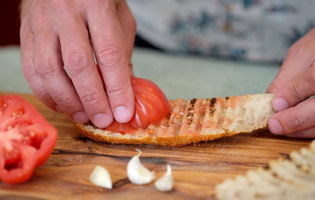3. Tomaten gnis så mot brødet. Skvis tomaten lett mellm fingrene slik at kjerner fester seg på brødet.
