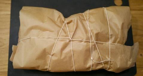 Pakk inn lammet i bakepapir og legg så et nytt papir over slik at pakken er tett og dampen forblir inne i pakken. Bind hyssing rundt pakken.