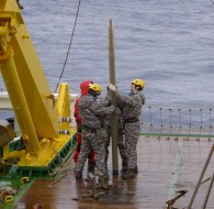 Marine technicians holding a core liner with sediment after recovery